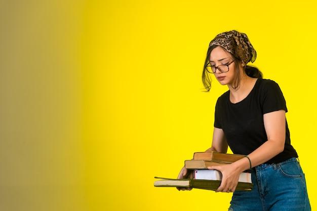 Giovane studentessa in occhiali tenendo i suoi libri su sfondo giallo. Foto Gratuite