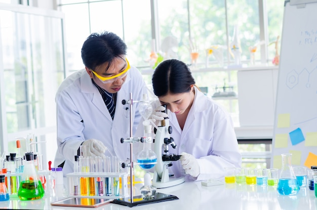 Young scientist looking through a microscope in a laboratory. young scientist doing some research. Premium Photo