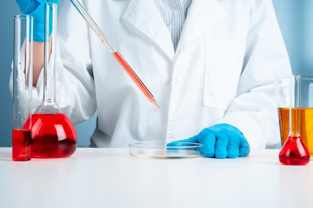 Young scientist with test tube making research in clinical laboratory Premium Photo