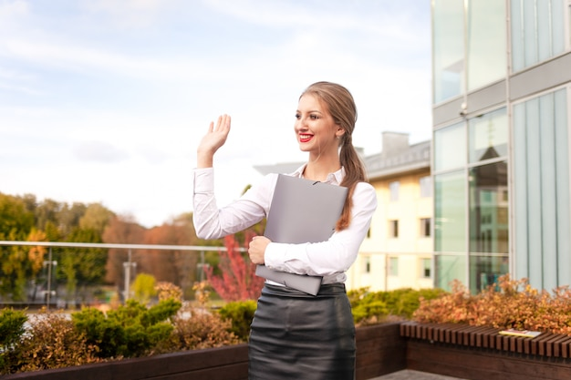 Young secretary with a folder in her hands waving. positive business woman waving hello Premium Photo