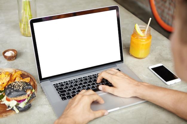 Giovane lavoratore autonomo che lavora al suo progetto su laptop generico mentre era seduto al caffè e utilizzando la connessione wi-fi gratuita. studente maschio che passa in rassegna internet o che controlla email sul dispositivo elettronico durante il pranzo Foto Gratuite