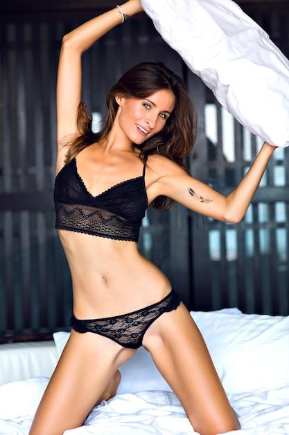 Молодая чувственная брюнетка женщина играет с подушкой, развлекается по утрам, в потрясающем сексуальном черном белье, в будуарном стиле Бесплатные Фотографии