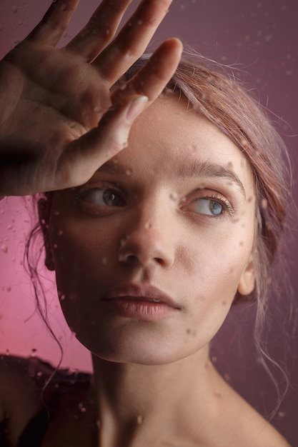 Young sensual girl puts her face on her hand and leans on glass on which blurred drops of water flow down. sad concept Premium Photo