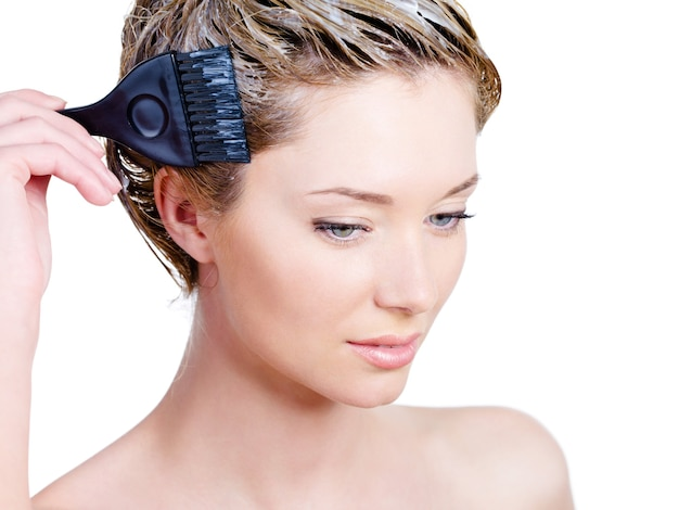 Молодая спокойная женщина, окрашивающая волосы щеткой Бесплатные Фотографии