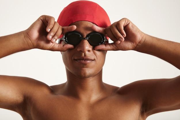 Giovane nuotatore afroamericano serio nel berretto rosso che indossa gli occhiali da nuoto neri su fondo bianco Foto Gratuite