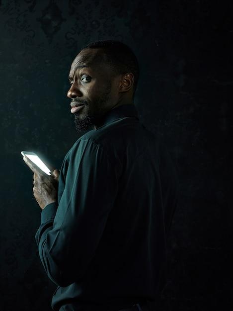 검은 스튜디오 배경에 휴대 전화로 얘기하는 동안 생각하는 젊은 심각한 흑인 아프리카 남자 무료 사진