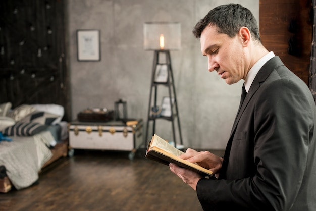 Young serious businessman reading book Free Photo