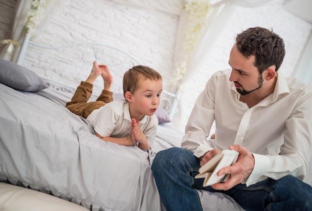 若い真面目な父親は、彼の手にカレンダーを持っている彼の好奇心旺盛な幼い息子と話している Premium写真
