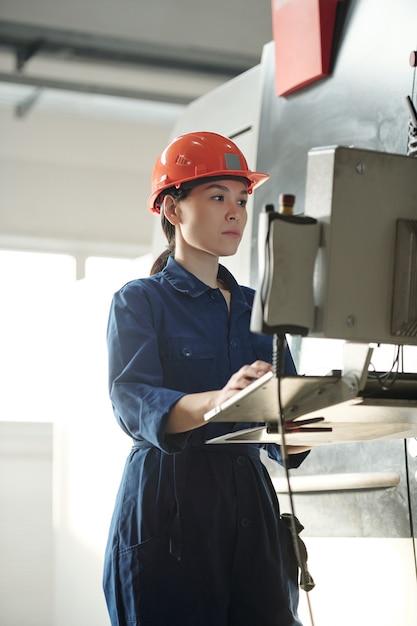 기술 데이터로 작업하는 동안 제어판의 화면을보고 유니폼과 헬멧에 젊은 심각한 여성 노동자 프리미엄 사진