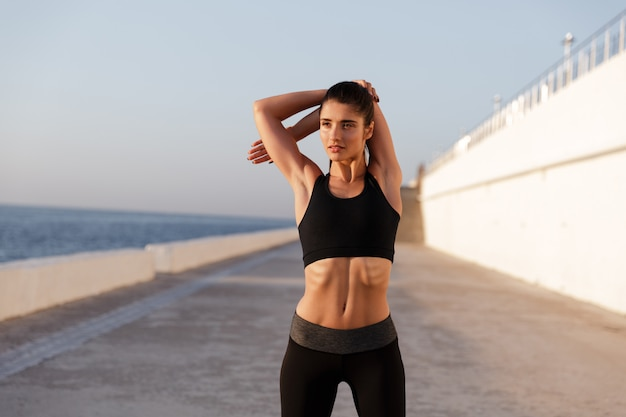 Young serious healthy woman stretching and training in morning Free Photo