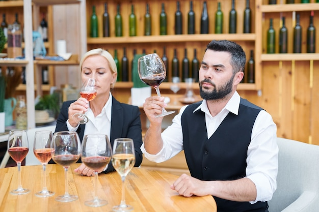 Young serious male cavist and his colleague checking smell and flavor of several new sorts of wine in cellar Premium Photo
