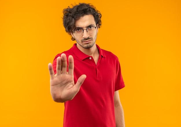 Молодой серьезный человек в красной рубашке с оптическими очками жестами останавливает знак рукой, изолирован на оранжевой стене Бесплатные Фотографии