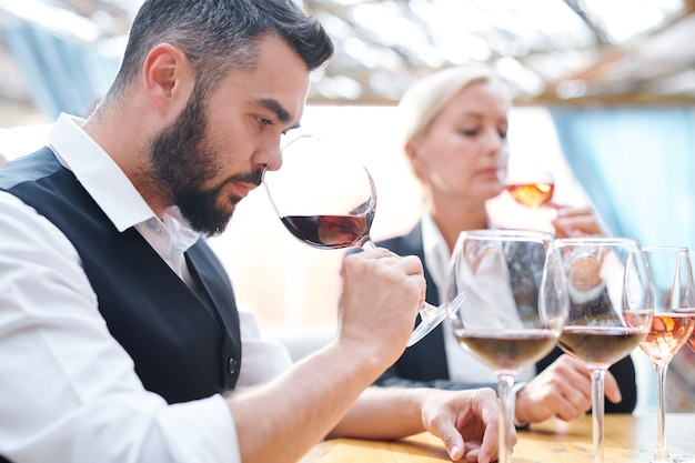 Young serious sommelier feeling smell of red wine while holding wineglass by his nose during work in cellar Premium Photo