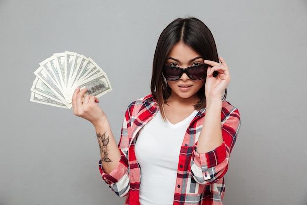 灰色の壁にお金を置く深刻な女性 無料写真