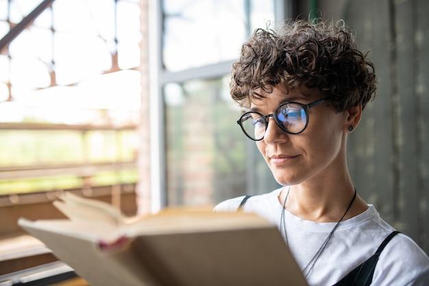 自宅で余暇を過ごしながら小説のページを見て茶色の巻き毛を持つ深刻な女性 Premium写真