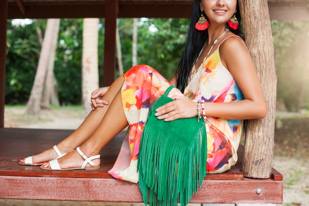Young sexy beautiful woman in colorful dress, summer hippie style, tropical vacation, green handbag with fringe, accessories, hands close up with bracelets, fingers, manicure Free Photo