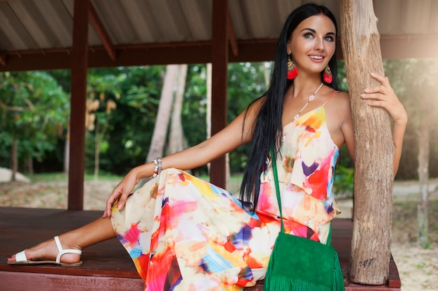 Young sexy beautiful woman in colorful dress, summer hippie style, tropical vacation, tanned legs, sandals, green handbag with fringe, accessories, smiling, happy Free Photo