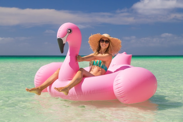 Young and sexy girl having fun and laughing on an inflatable giant pink flamingo float mattress in a bikini on the sea. attractive tanned woman lies in the sun on vacation Premium Photo