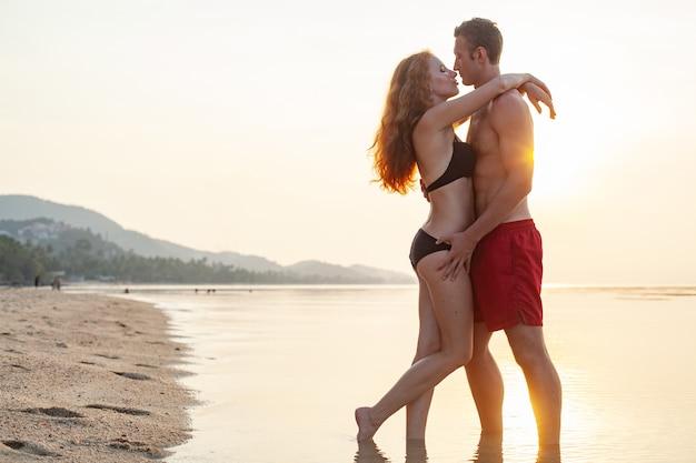 Молодая сексуальная романтическая влюбленная пара счастлива на летнем пляже, вместе веселясь в купальных костюмах Бесплатные Фотографии