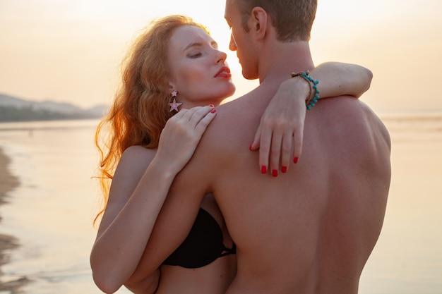 一緒に水着を着て楽しんで夏のビーチで幸せな恋に若いセクシーなロマンチックなカップル 無料写真