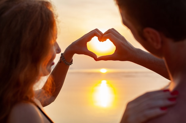 Giovane coppia romantica sexy innamorata felice sulla spiaggia d'estate insieme divertendosi indossando costumi da bagno mostrando il segno del cuore sul sundet Foto Gratuite