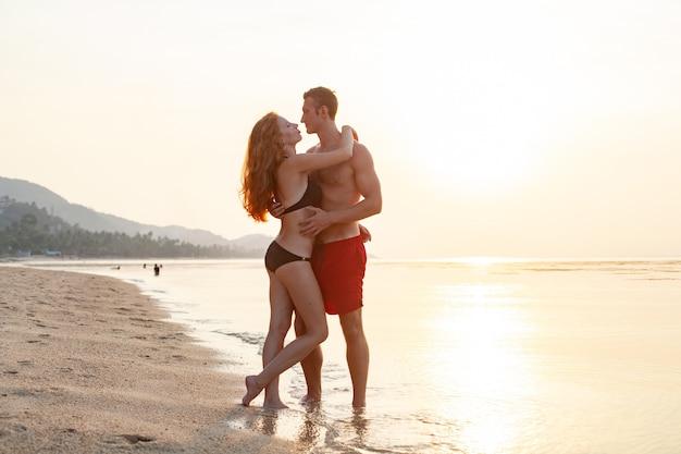 Giovane coppia romantica sexy innamorata felice sulla spiaggia estiva insieme divertendosi indossando costumi da bagno Foto Gratuite