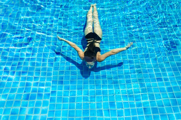 Young sexy slim woman relaxing in swimming pool with crystal blue water Premium Photo