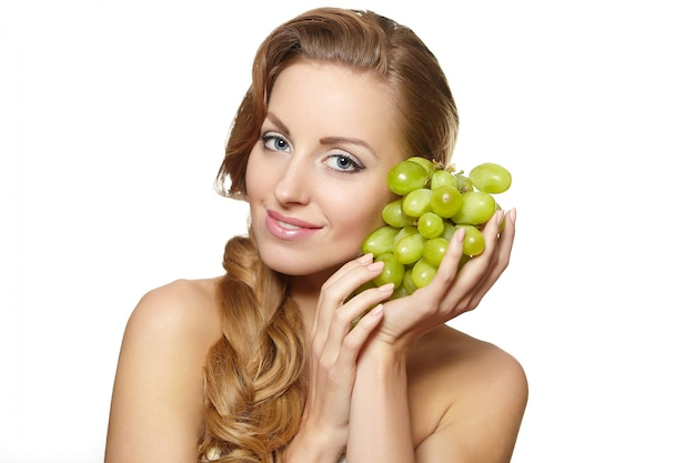 Young sexy smiling beautiful  woman holding a bunch of grape in her hands with long hair isolated on white Free Photo