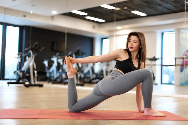 Young sexy woman doing stretching exercises in gym Premium Photo