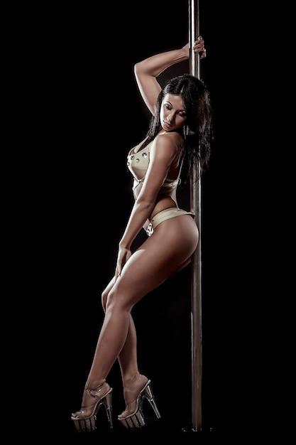 若いセクシーな女性は黒い背景に対してポールダンスを行使します 無料写真