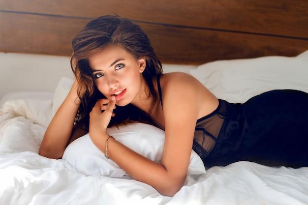 ベッドでポーズをとって黒いランジェリーの若いセクシーな女性 無料写真