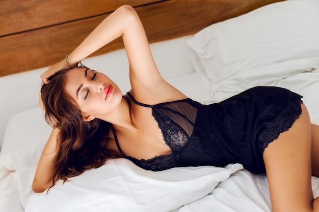 침대에서 포즈 검은 란제리에 젊은 섹시 한 여자 무료 사진