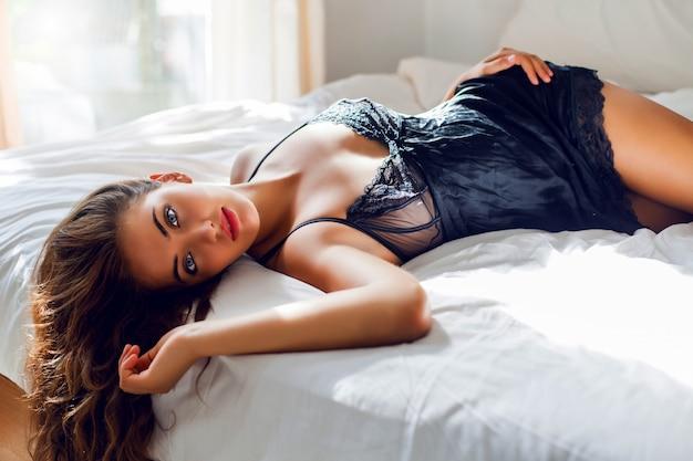 Молодая сексуальная женщина в черном белье позирует в постели Бесплатные Фотографии