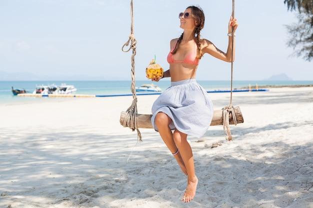 Giovane donna sexy che si siede sull'altalena sulla spiaggia tropicale, vacanze estive, stile di moda, gonna, top bikini, bere cocktail di cocco, sorridente, rilassante Foto Gratuite