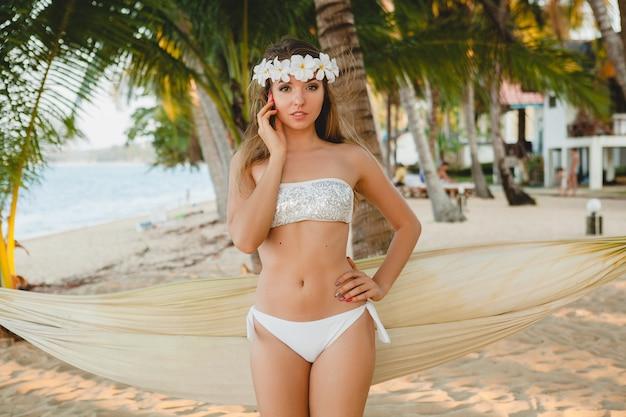 Giovane donna sexy in costume da bagno bikini bianco in posa sulla spiaggia tropicale, palme, hawaii, fiori nei capelli, sensuale, corpo snello, soleggiato, godendo le vacanze, viaggiando sull'isola Foto Gratuite