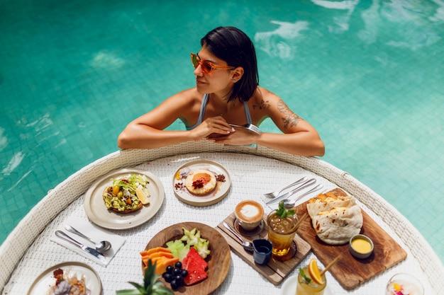 Giovane donna sexy con il tatuaggio in costume da bagno facendo colazione in una piscina privata. ragazza rilassante in piscina bevendo caffè e mangiando frutta. piatto di frutta, frullato a bordo piscina. Foto Gratuite