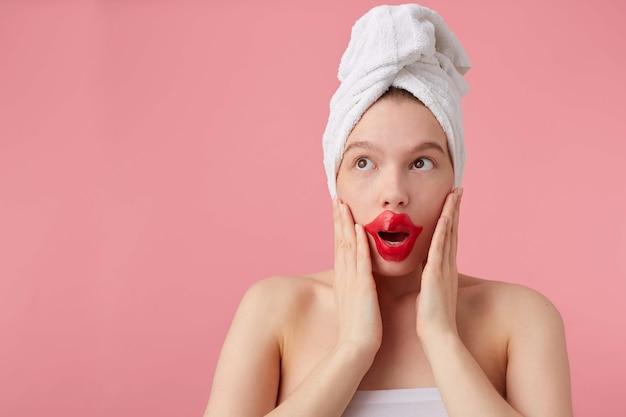 スパの後、頭にタオルと唇のパッチを当ててショックを受けた若い女性は、目を大きく開いて目を離し、新しいゴシップを聞き、手のひらで頬に触れ、立ちます。 無料写真