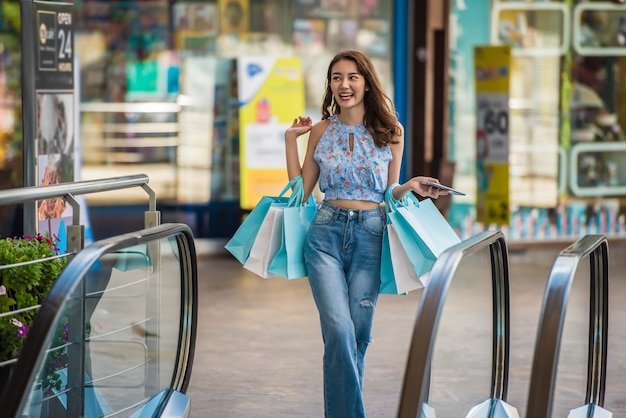 Young shopping woman holding paper bags at shopping mall, travelling shopping concept. Premium Photo