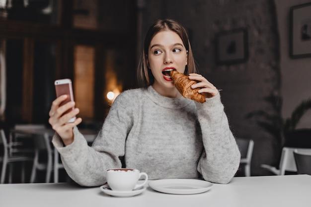 회색 셔츠를 입은 젊은 단발 소녀가 밝은 카페에서 선명한 크로와상을 물고 셀카를 찍습니다. 무료 사진