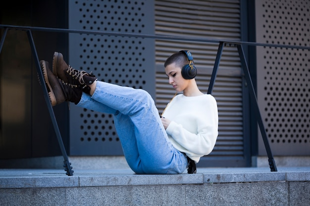 Young short-haired woman sitting and listening to music outdoors Free Photo