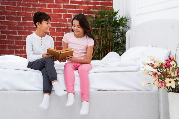 Young siblings at home on bed riding Free Photo
