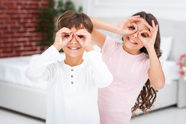 Young siblings making binocular with hands Free Photo