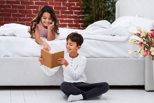 Young siblings reading together stories Free Photo