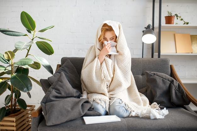 Молодая больная женщина с платком, сидя на диване под одеялом Premium Фотографии