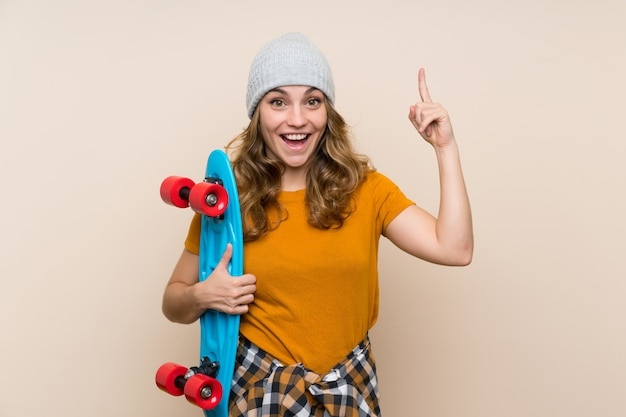 Young skater blonde girl over isolated wall pointing up a great idea Premium Photo