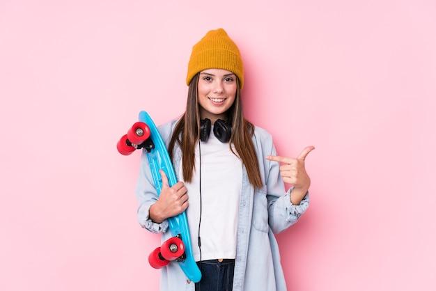 Молодая фигуристка держит человека на коньках, указывая рукой на пространство для копирования рубашки, гордая и уверенная в себе Premium Фотографии