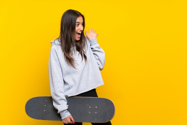 Young skater woman  isolated on yellow  with surprise facial expression Premium Photo