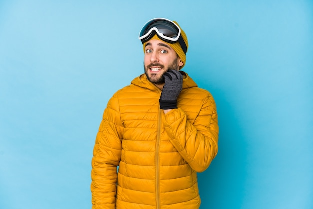 若いスキーヤー白人男は、神経質で非常に心配で爪をかむを分離しました。 Premium写真