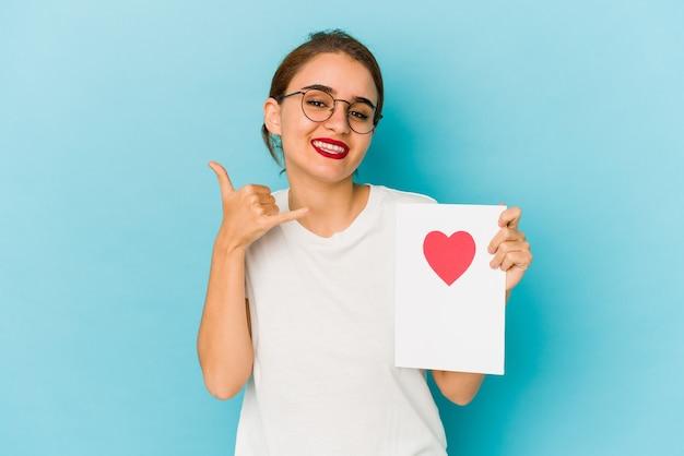 指で携帯電話の呼び出しジェスチャーを示すバレンタインデーカードを保持している若い細いアラブの女の子。 Premium写真