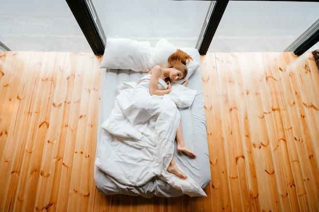毛布と枕の白いベッドで横になっていると眠っている若い細い美しい裸足少女。朝はソファでリラックス。木製の床と大きな窓付きのスタジオアパートで休んで生姜女性 Premium写真
